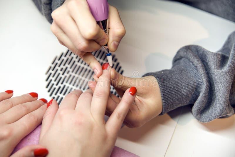 取消老指甲油,修指甲 碾碎钉子 去除钉子板材与一台铣床 免版税库存照片