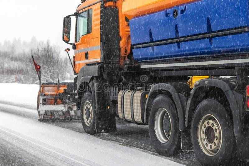 取消肮脏的雪的除雪机卡车从城市街道或高速公路在大雪以后 交通路情况 天气 图库摄影