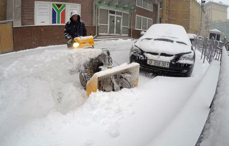 取消雪的人与吹雪机 免版税库存图片