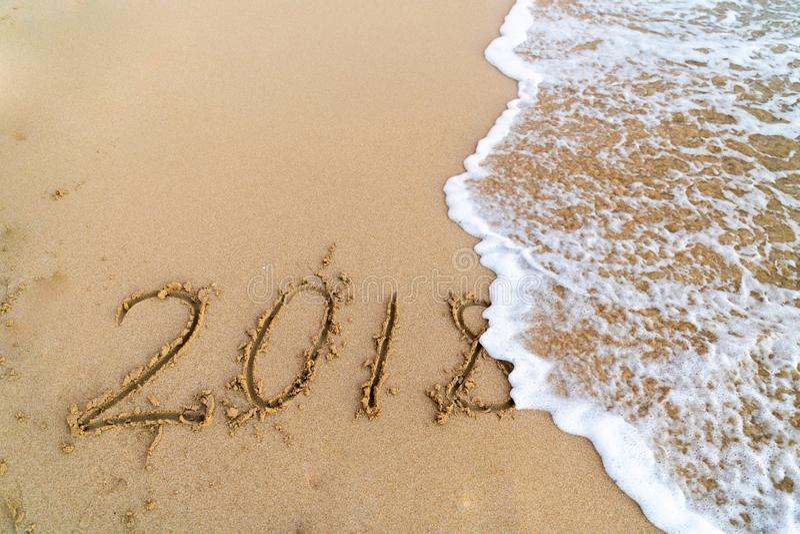 取消2018年的波浪写在沙子 免版税库存图片