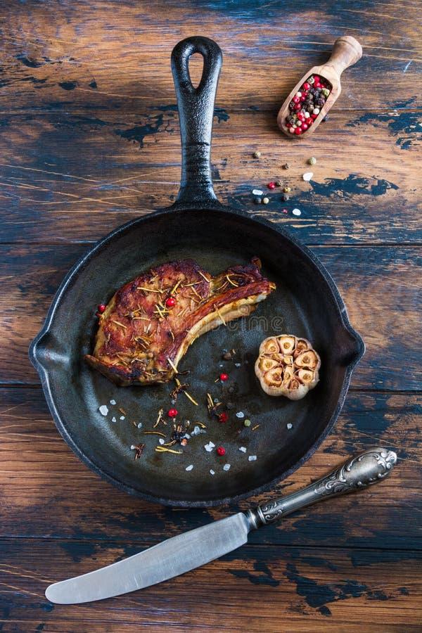 取笑眼睛猪肉牛排和被烘烤的大蒜在黑铸铁长柄浅锅在木土气桌上 红辣椒,葡萄酒刀子,顶视图 库存照片