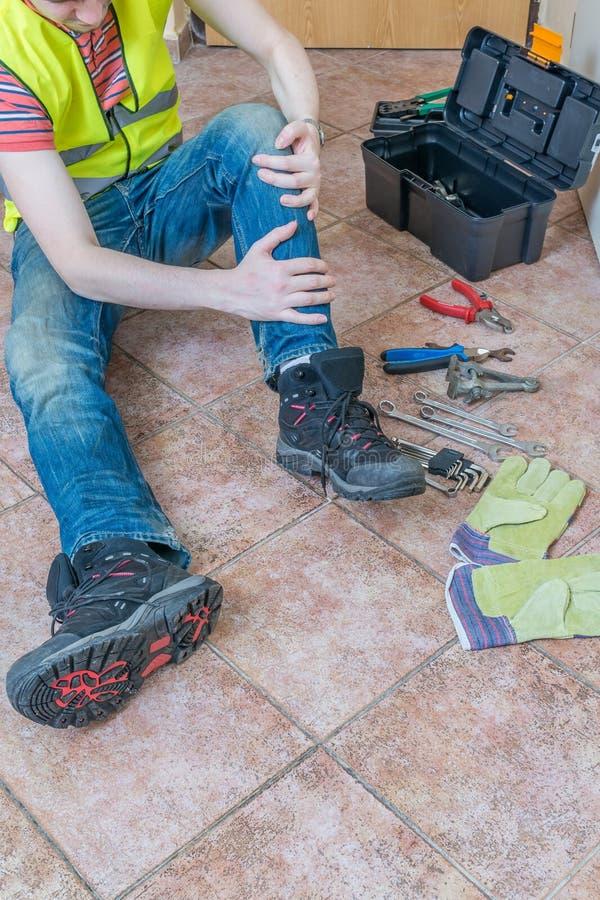 受伤的工作者有事故 受伤的腿或膝盖 库存图片