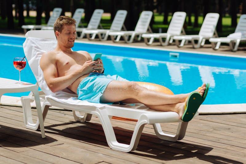 变冷兴旺的商人,当晒日光浴在水池附近时 免版税图库摄影