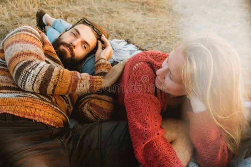 变冷和拥抱在草的毯子的行家夫妇在sunri 库存图片