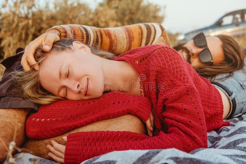变冷和拥抱在草的毯子的行家夫妇在sunri 库存照片