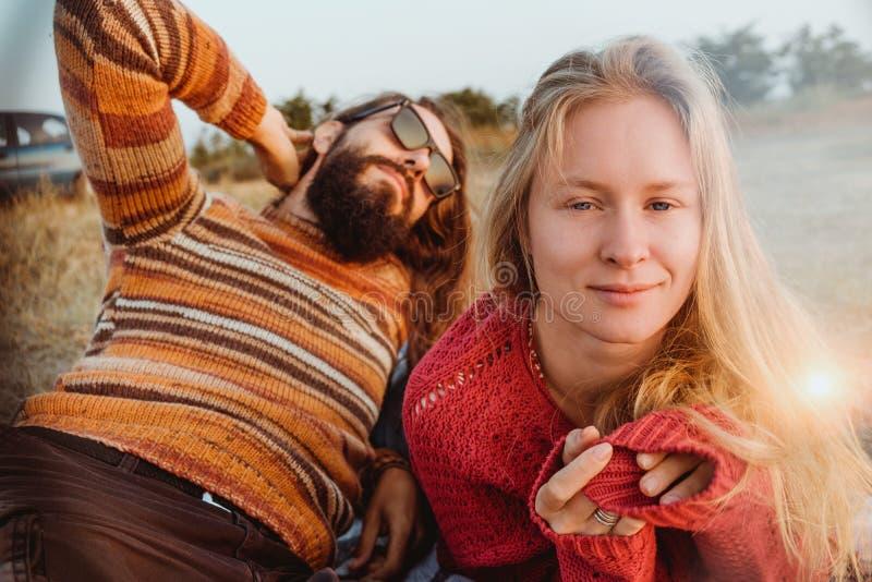 变冷和拥抱在草的毯子的行家夫妇在sunri 免版税库存图片