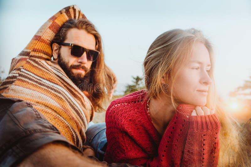 变冷和拥抱在草的毯子的行家夫妇在sunri 免版税库存照片