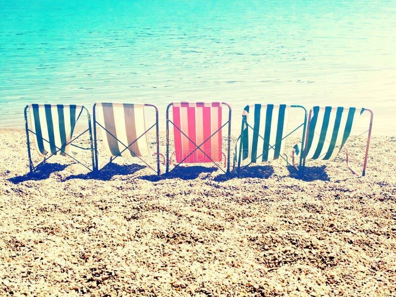 变冷在与减速火箭的条纹太阳床的海滩 库存图片