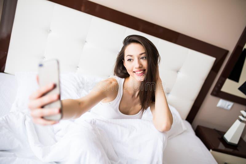 变冷在床上的selfie画象甜快乐的女孩早晨 库存照片