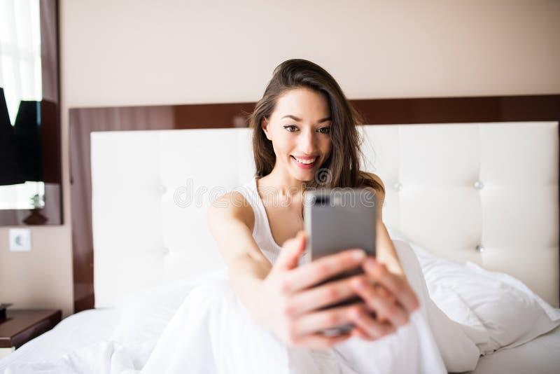 变冷在床上的selfie画象甜快乐的女孩早晨 免版税库存图片