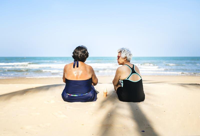 变冷在海滩的资深朋友 免版税库存图片
