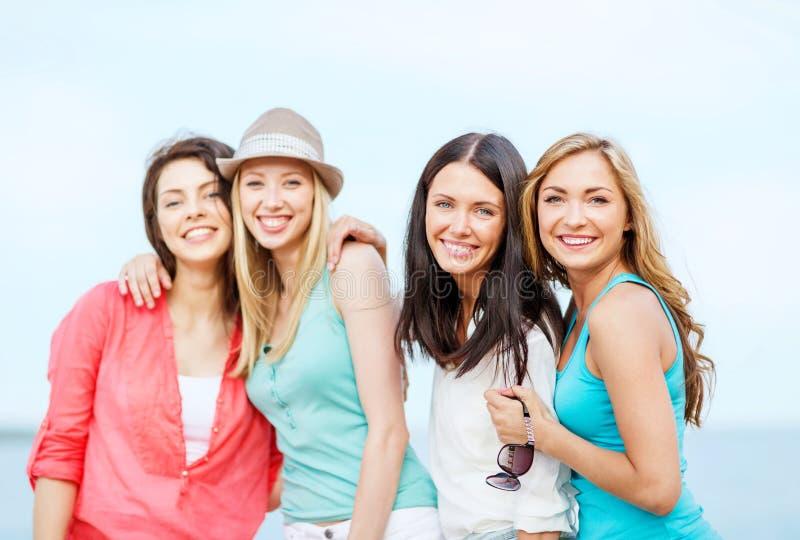 变冷在海滩的小组女孩 免版税库存图片