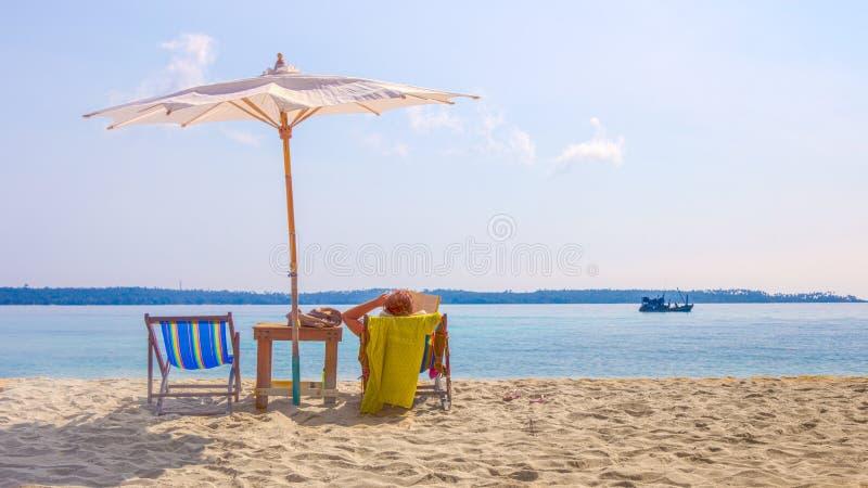 变冷在海滩睡椅的夫人在一个美丽的海滩在wh下 免版税库存照片
