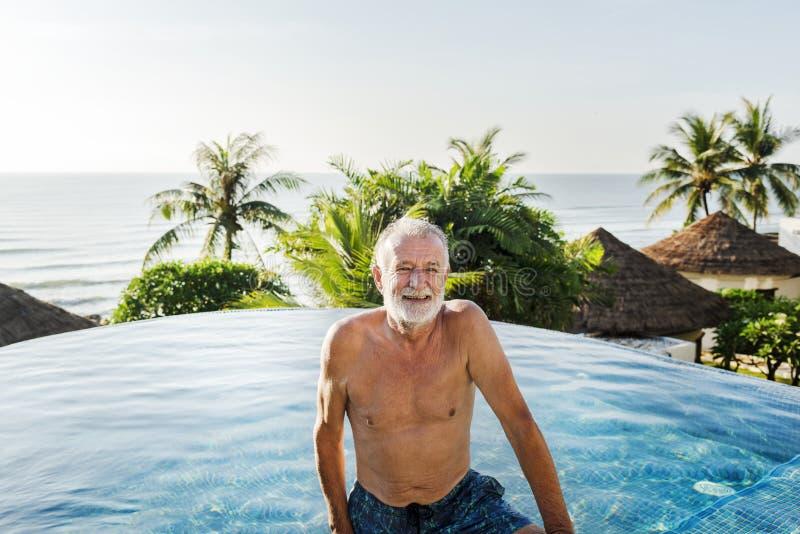变冷在游泳池的老人 库存图片