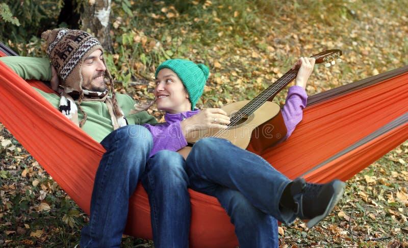 变冷在秋天森林妇女使用的吊床的愉快的夫妇 免版税库存图片