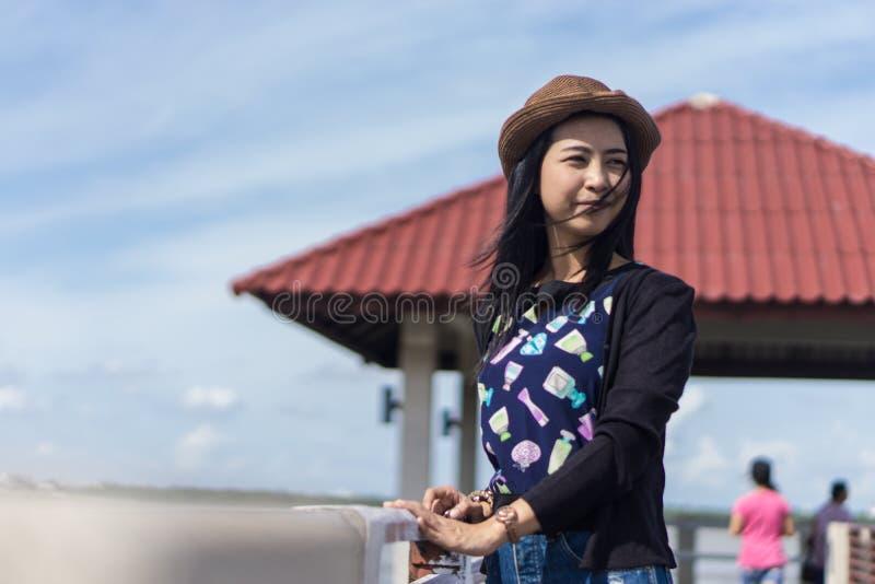 变冷在阳光下在河旁边的年轻亚裔旅客女孩和江边亭子和红色屋顶 库存照片
