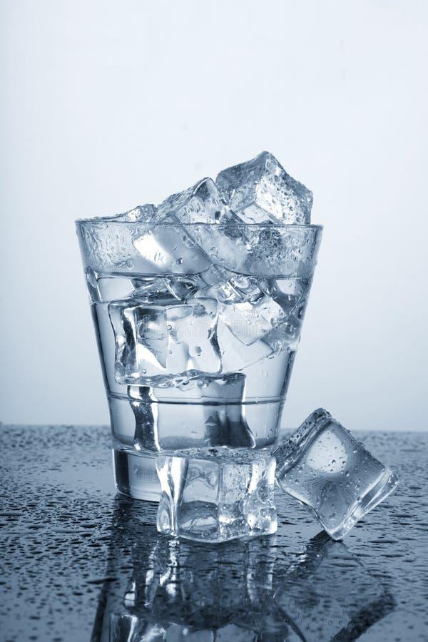 变冷的杯与艾斯・库伯和水下落的水 免版税库存照片