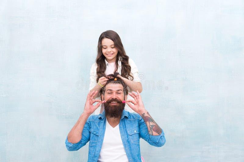 变动发型 培养女孩 创造滑稽的发型 做发型的孩子称呼父亲胡子 是父母手段 图库摄影