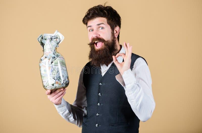变得富有 打手势好与在玻璃瓶子的金钱的富有的商人 有金钱现金的有胡子的有钱人 当成为的a 免版税库存照片