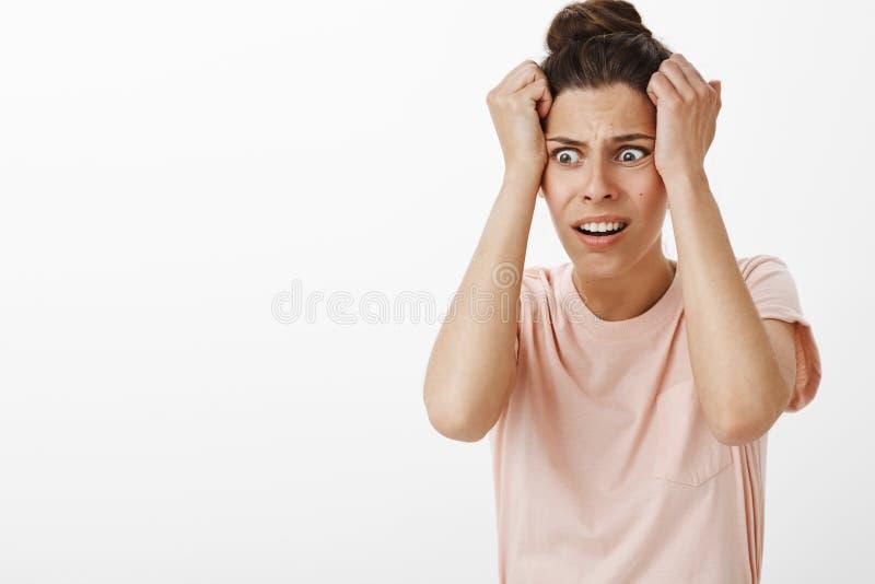 变得极度兴奋的女孩出发恐慌作为体会她怀孕感觉在皱眉的头的担心和急切举行的手 免版税库存照片