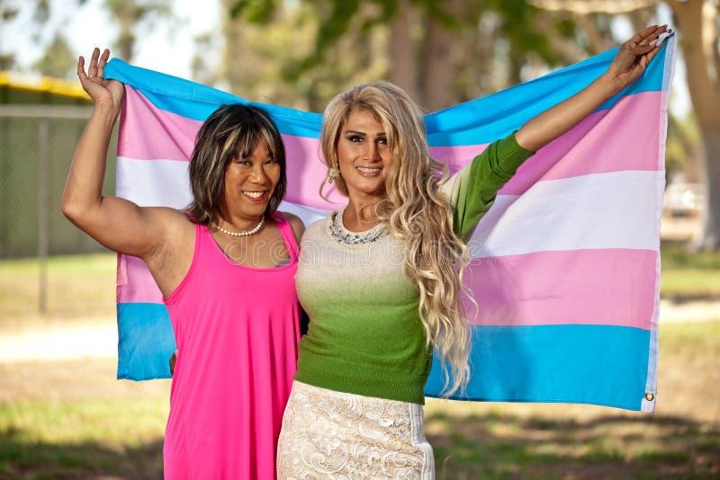 变性男性给骄傲地拿着自豪感旗子的女性 免版税库存图片