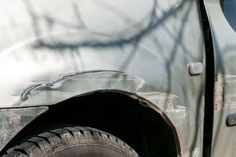 变成银色有消弱的铝金属身体被抓的和削皮油漆的损坏的汽车 库存图片