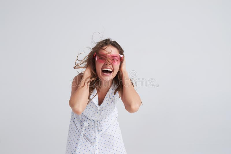 变桃红色的太阳镜的激动的女孩疯狂 库存照片