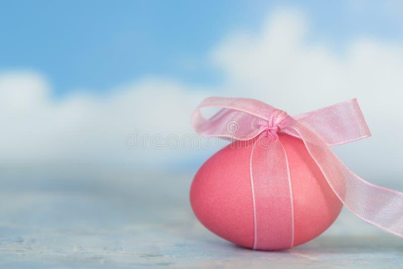 变粉红色与丝带的被绘的复活节彩蛋反对模糊的蓝天 免版税库存照片