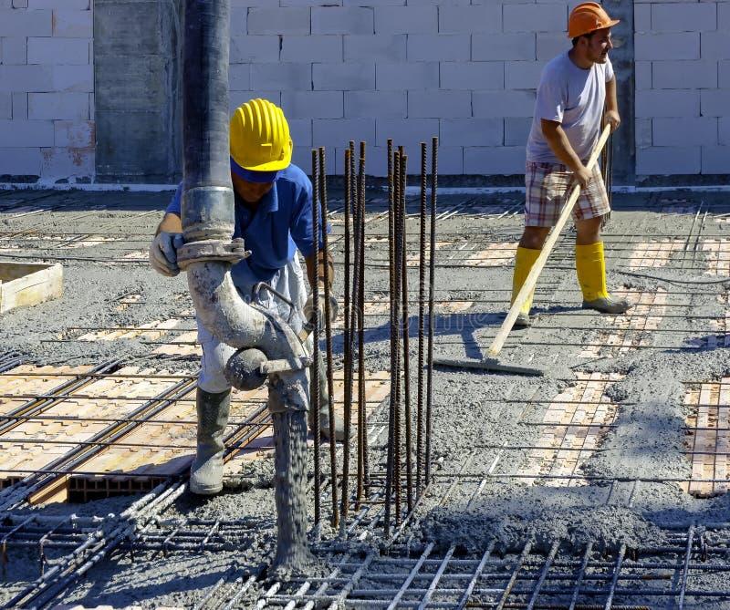 变紧密液体水泥以增强形式的建筑工人 库存照片