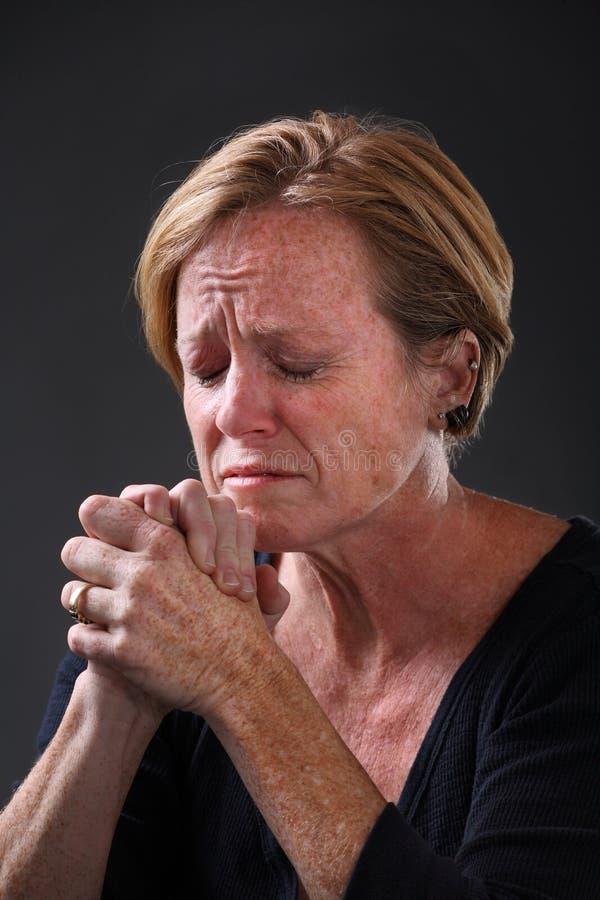 变老的中间祈祷的妇女 库存照片