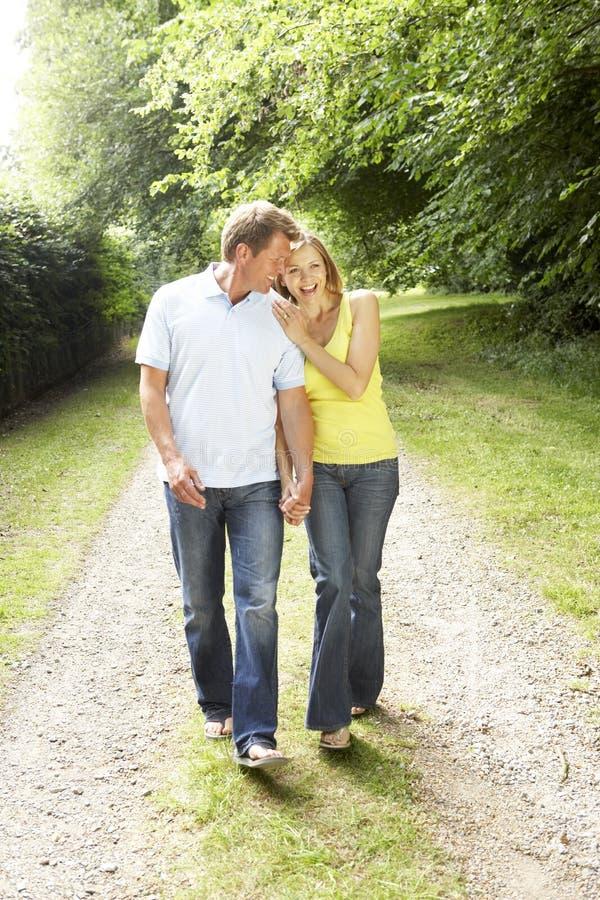 变老的乡下夫妇中间走 免版税库存照片