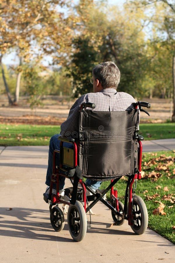 变老的人中间名轮椅 免版税库存照片