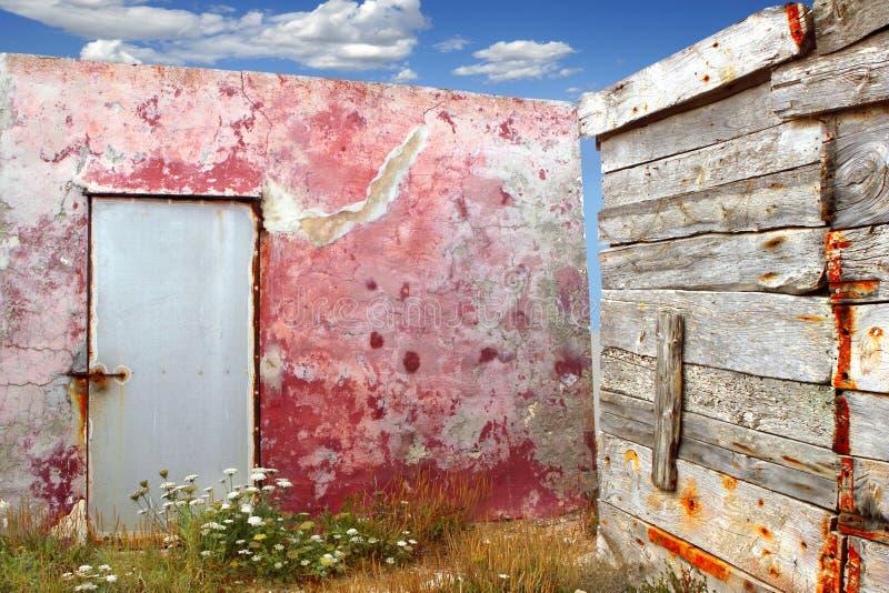 变老的壁角grunge红色墙壁被风化的木头 免版税库存图片