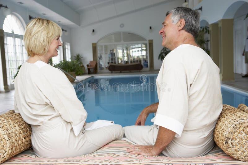 变老的夫妇中间池松弛游泳 免版税库存照片