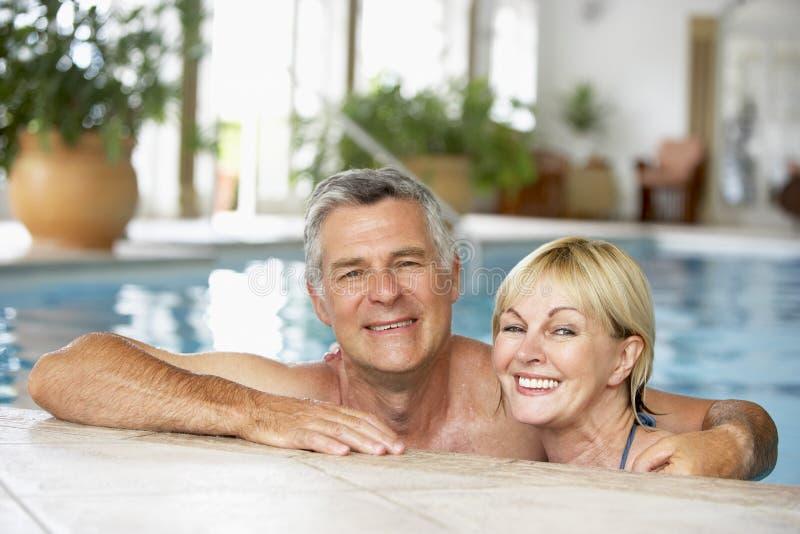 变老的夫妇中间池游泳 库存照片