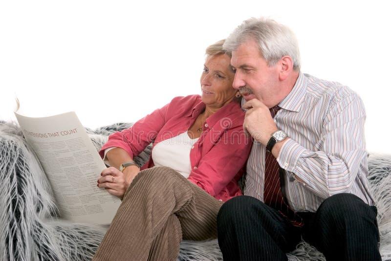 变老的夫妇中间读取一起 库存照片