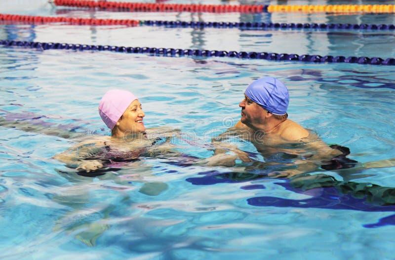 变老的夫妇中间池游泳 免版税库存照片
