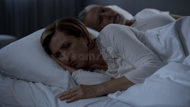变老的夫妇说谎失眠在床,妇女上转动了回到人,怨气 库存照片
