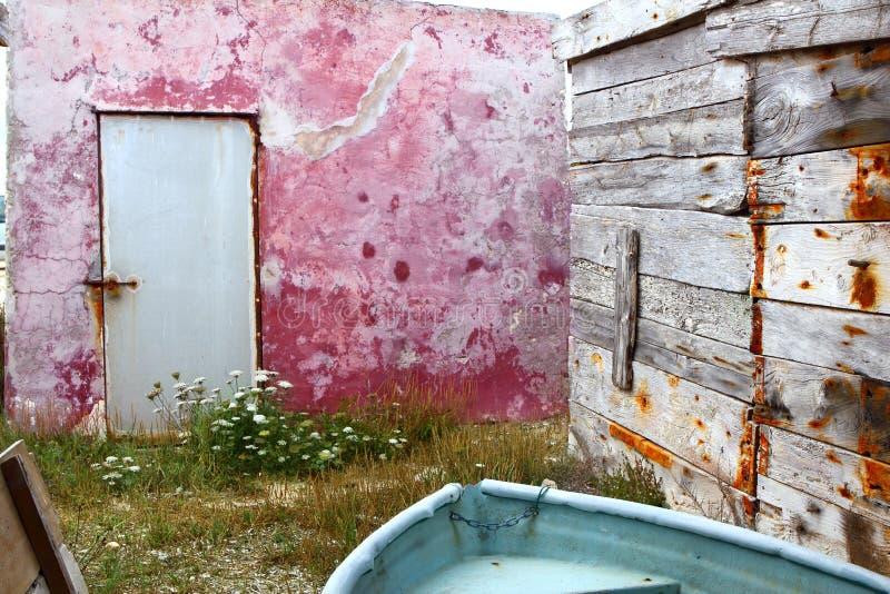 变老的小船grunge红色墙壁被风化的木头 免版税库存照片