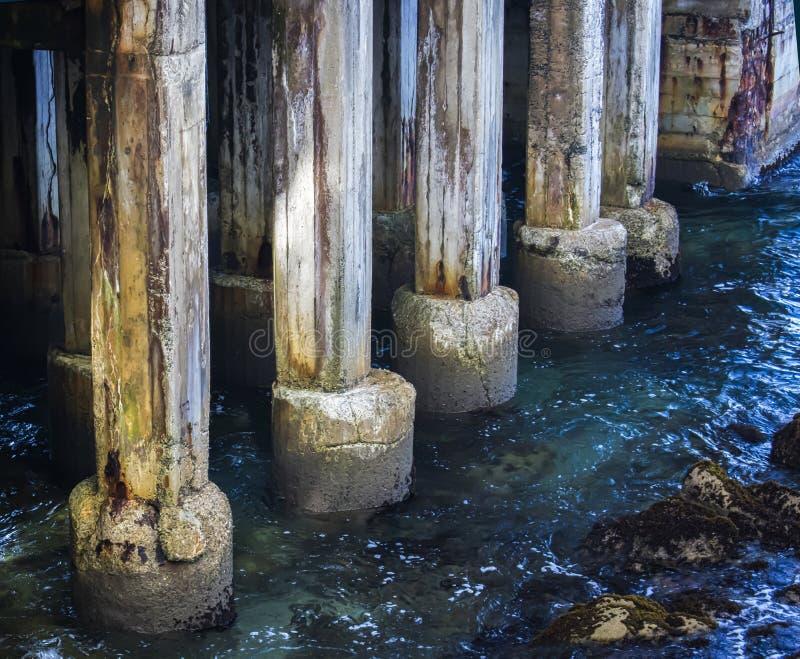 变老的码头打桩的关闭在蓝色清楚的海 免版税库存图片