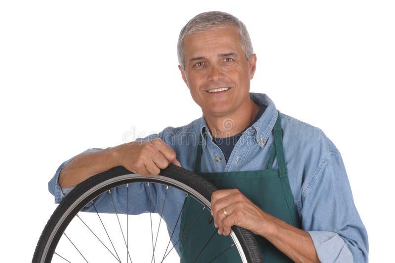 变老的自行车人中间修理 免版税图库摄影