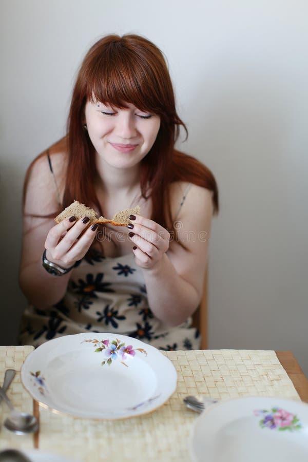 变老的面包吃青少年的女孩 免版税库存照片