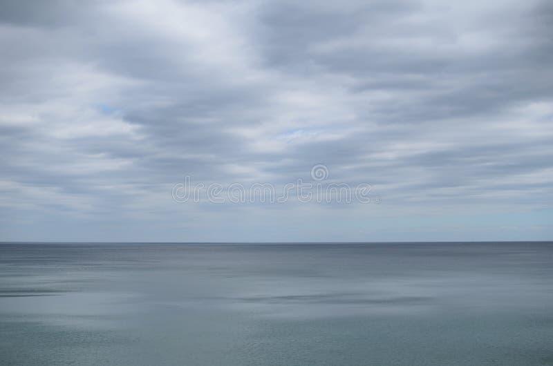 变苍白在昏暗的灰色海水的多云天空 库存图片