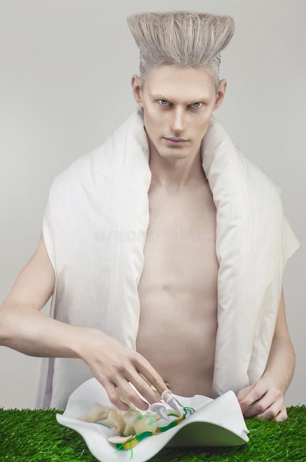变苍白白色成套装备的白肤金发的人吃健康食品的 免版税图库摄影