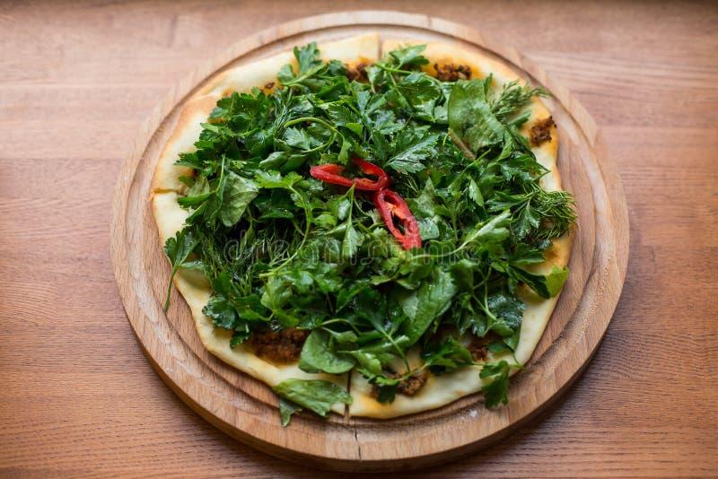 变薄亚美尼亚皮塔饼面包用乳酪、胡椒和草本支持的 在板材的Lamadjo 关闭 顶视图 免版税库存图片