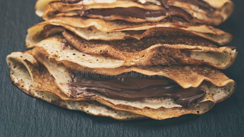 变薄绉纱或俄式薄煎饼与巧克力奶油在板岩板 免版税库存照片