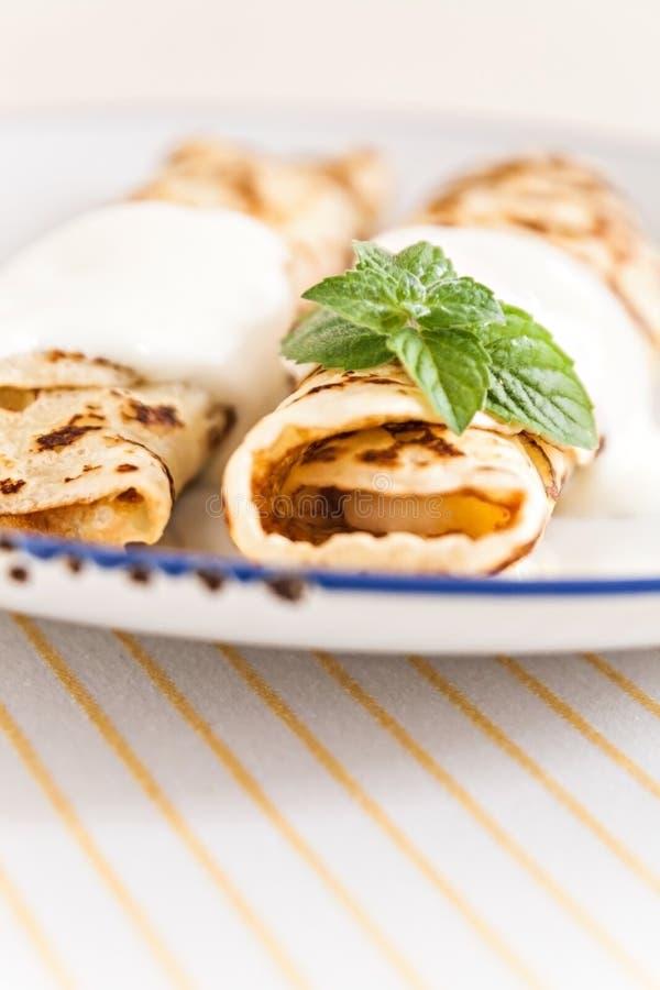 变薄绉纱滚动的薄煎饼用在板材的酸性稀奶油薄菏 免版税库存照片