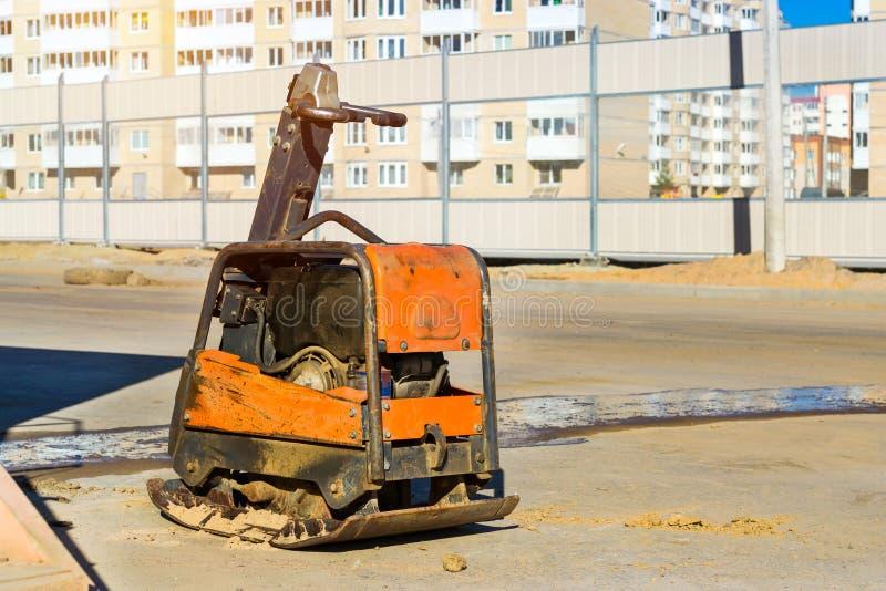 变紧密的土壤的手工猛撞的机器在路 免版税库存照片