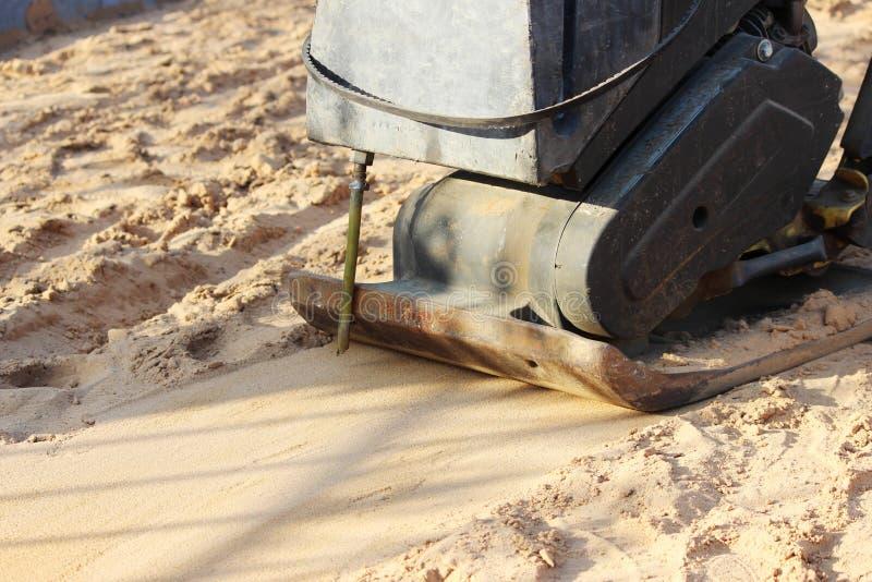 变紧密的沙子的Vibro路辗在放置铺路板前在边路的修理期间在城市 库存照片