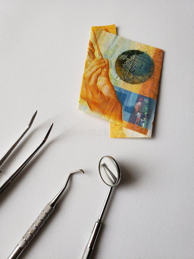 口头回顾和十法郎瑞士钞票的牙医器物  库存照片